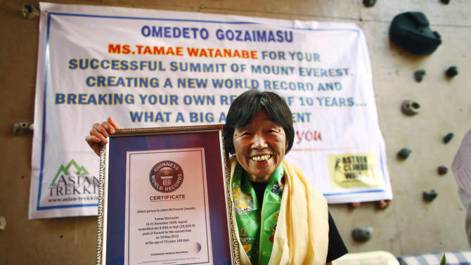 Japanese climber Tamae Watanabe poses with a replica of the Guinness World Record certificate during a press conference organized by the Asian Trekking to felicitate her in Katmandu, Friday, May 25. 2012. Watanabe, 73, has made history by becoming the oldest woman to scale the world's highest mountain, Mount Everest, bettering a record, she herself set a decade ago. (AP Photo/Niranjan Shrestha)