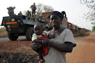 A Malian woman carries her child as she walks by a convoy of French army vehicules arriving in Sevare, in the Mopti region of Mali, on February 1, 2013