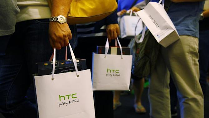 Customers hold bags containing their HTC One mobile phone purchases during the first day of public sales in Jakarta