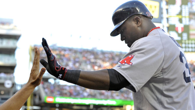 Boston Red Sox's David Ortiz is congratulated in the dugout following his two-run home run off Minnesota Twins pitcher Scott Baker in the sixth inning of a baseball game Monday, Aug. 8, 2011, in Minneapolis. (AP Photo/Jim Mone)