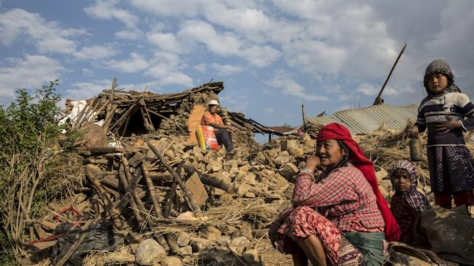 Red Cross handout picture of people sitting on the rubble of a collapsed building following an earthquake in Kathmandu