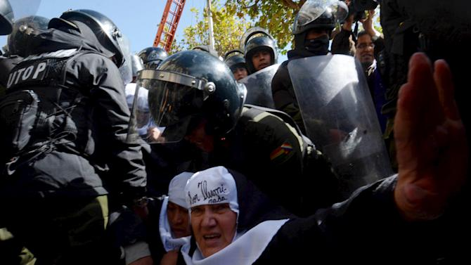 Police officers try to break up a protest by activists dressed as nuns, at Murillo square in La Paz