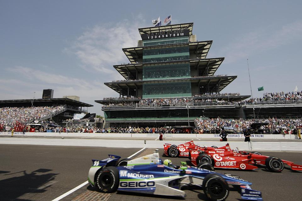 Dario Franchitti, center, of Scotland, crosses the finish line ahead of Scott Dixon, rear, of New Zealand, and Tony Kanaan, bottom, of Brazil, to win IndyCar's Indianapolis 500 auto race at Indianapolis Motor Speedway in Indianapolis, Sunday, May 27, 2012. (AP Photo/Darron Cummings)