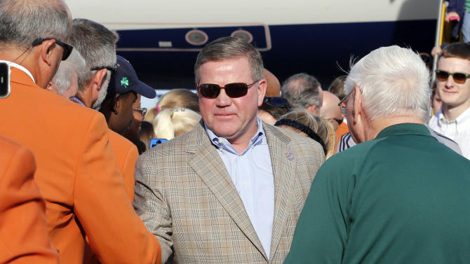 Notre Dame head coach Brian Kelly is greeted by BCS officials as he arrives in Fort Lauderdale, Fla., Wednesday, Jan. 2, 2013. Notre Dame is scheduled to play Alabama in the BCS national championship NCAA college football game next Monday in Miami. (AP Photo/Alan Diaz)