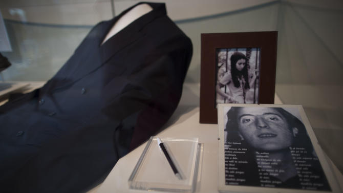 """A picture of Argentina's late President Nestor Kirchner, right, his pen, his suit and a picture of his wife, current President Cristina Fernandez, top, sit on display at the Bicentennial Museum in Buenos Aires, Argentina, Wednesday, Nov. 21, 2012.  A documentary film titled """"Nestor Kirchner"""" hits the theaters on Thursday, the latest example of an ongoing effort to exalt the late president's memory, seeking to match the level of Juan Domingo Peron.  Streets, hospitals, tunnels and even a soccer tournament is named after Nestor Kirchner, who served as president from 2003 to 2007 and died at the age of 60 on Oct. 27, 2010. (AP Photo/Natacha Pisarenko)"""