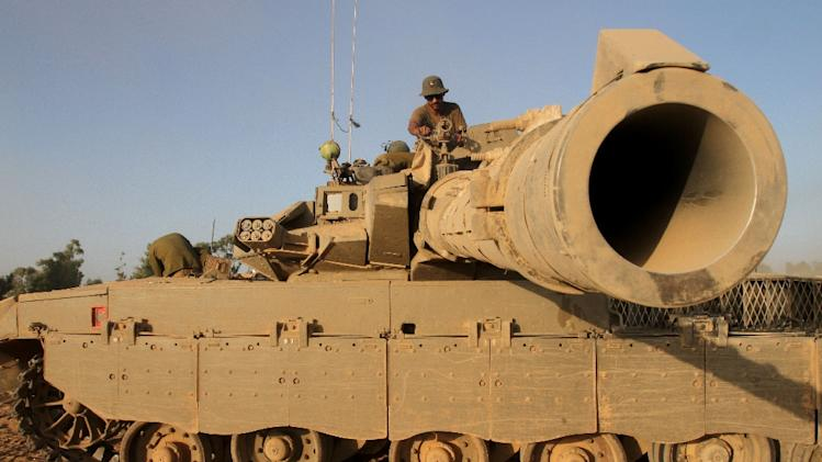 An Israeli soldier sits on top of a Merkava tank along the border between Israel and the Hamas-controlled Gaza Strip, on July 30, 2014