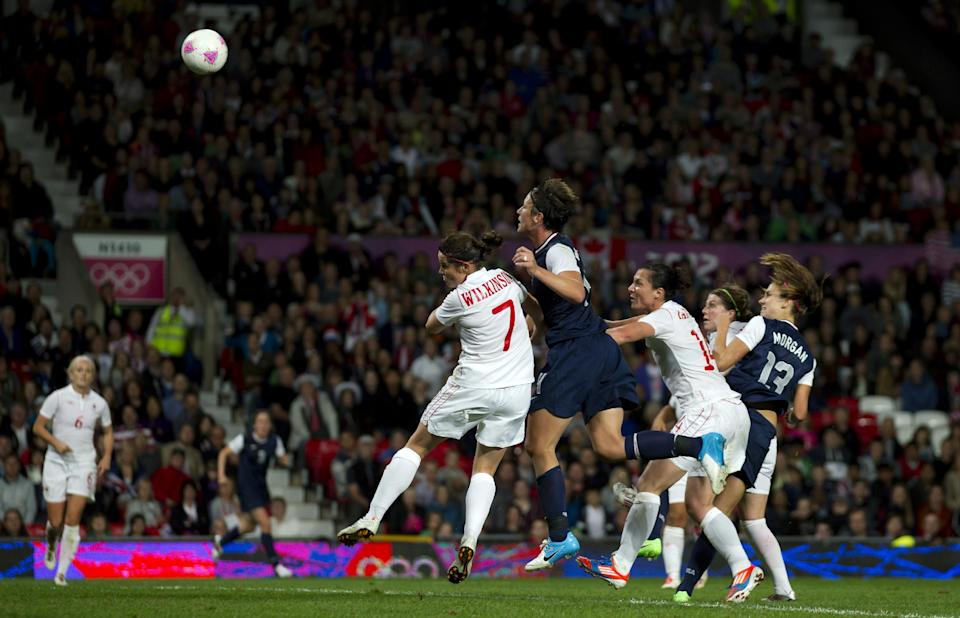 United States' Alex Morgan, right, scores the winning goal against Canada during their semifinal women's soccer match at the 2012 London Summer Olympics, Monday, Aug. 6, 2012 at Old Trafford Stadium in Manchester, England. (AP Photo/Jon Super)