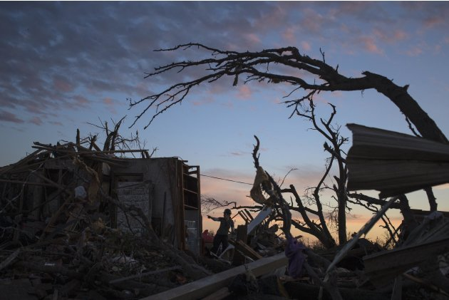 A woman searches for possessions at sunset after the suburb of Moore, Oklahoma was left devastated by a tornado