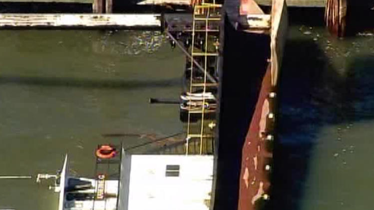 In this image provided by WABC-TV an overturned tug boat sits in the water near Liberty Island in New York on Friday, April 6, 2012. Three crew members were rescued after the boat tipped over while trying to lift something with a crane on the vessel. (AP Photo/WABC-TV)