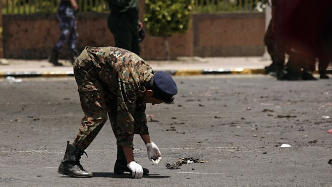 A policeman collects evidence at the site of a suicide bomb attack at a parade square in Sanaa, Yemen, Monday, May 21, 2012. Officials say Monday's bombing near Sanaa's presidential palace is one of the deadliest attacks in the city in months. (AP Photo/Hani Mohammed)