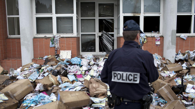 """A police officer stands in front of the headquarters of satiric French newspaper Charlie Hebdo, that """"invited"""" the Prophet Muhammad as a guest editor this week, in Paris, Wednesday, Nov. 2, 2011. A police official said the fire broke out overnight at the offices of Charlie Hebdo, and the cause remains unclear. No injuries were reported. The official spoke on condition of anonymity because an investigation into the fire is under way. (AP Photo/Thibault Camus)"""