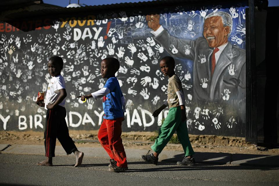 Children walk in front of a year old mural outside former South African President Nelson Mandela's former Alexandra township residence in Johannesburg, South Africa, Thursday June 13, 2013. Nelson Mandela remained hospitalized for the sixth day with an occurring lung infection. The latest government report says that he remains in a serious but stable condition. (AP Photo/Jerome Delay)