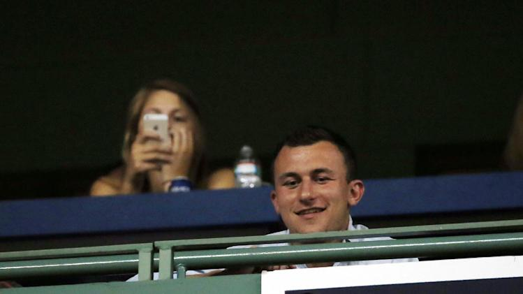Football quarterback Johnny Manziel watches from an upper box at Fenway Park during a baseball game between the Boston Red Sox and the Chicago White Sox in Boston, Wednesday, July 9, 2014. (AP Photo/Elise Amendola)