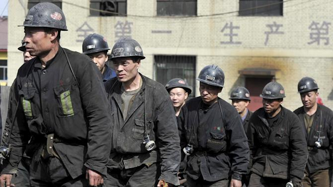 Rescuers walk past outside a coal mine after a flooding incident in Datong