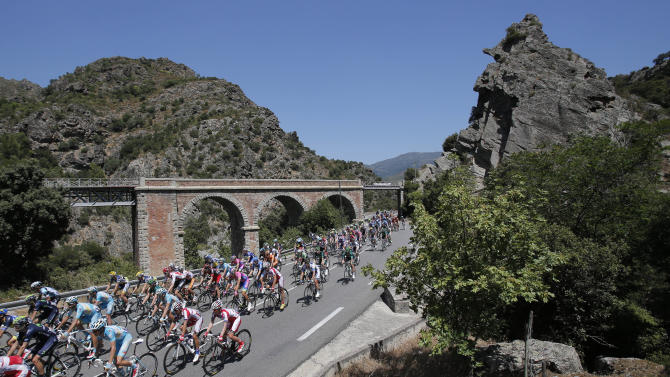 The pack passes a railroad bridge near Ponte Leccia during the second stage of the Tour de France cycling race over 156 kilometers (97.5 miles) with start in Bastia and finish in Ajaccio, Corsica island, France, Sunday June 30, 2013. (AP Photo/Christophe Ena)