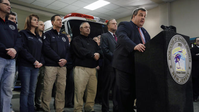 "Seaside Heights Mayor Bill Akers, third right, New Jersey Department of Environmental Protection Commissioner Bob Martin, second right, stand with Seaside Heights firefighters and first responders as they listen to New Jersey Gov. Chris Christie, right, announce his ""Hurricane Sandy Flood Map Regulations"" Thursday, Jan. 24, 2013, in Seaside Heights, N.J. The town, which was featured in the MTV reality show ""Jersey Shore"" sustained substantial damage to homes and its boardwalk during Superstorm Sandy. The guidelines will include where and how high to rebuild. (AP Photo/Mel Evans)"