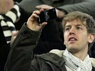 Red Bull's Formula One driver Sebastian Vettel of Germany (L) films with his mobile phone beside his girlfriend Hanna Prater as they attend the Spanish first division soccer match between Barcelona and Valencia at Nou Camp stadium in Barcelona February 19, 2012. REUTERS/Albert Gea/Files