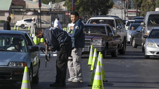 Motorists wait inside their cars to drop guns to waiting Los Angeles Police officials at the LA Memorial Sports Arena in Los Angeles Wednesday, Dec. 26, 2012. Los Angeles police are offering groceries for guns in a buyback program that was moved up in the wake of the Connecticut tragedy. Police officials will be accepting weapons Wednesday at the LA Memorial Sports Arena and the Van Nuys Masonic Temple. Weapons can be turned in with no questions asked. Handguns, rifles and shotguns can be exchanged for $100 Ralphs grocery store gift cards. An automatic weapons will earn a $200 card. (AP Photo/Damian Dovarganes)