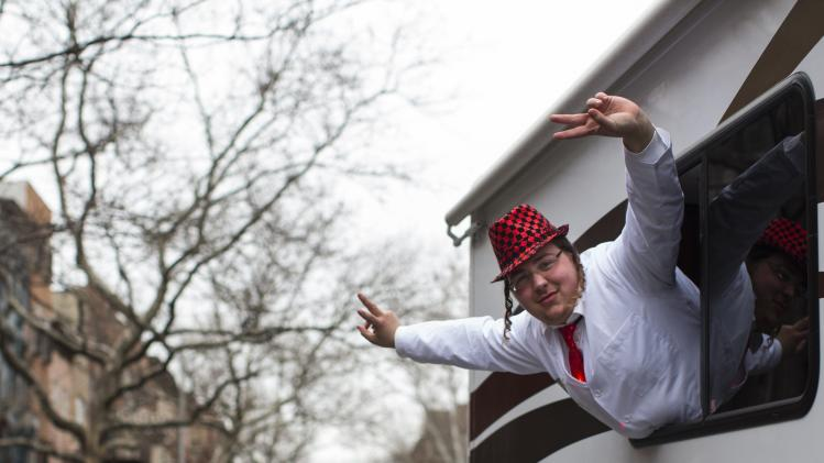 A man leans out of a camper van window during the Jewish holiday of Purim in the South Williamsburg suburb of New York