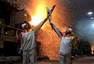 Olympic torchbearers at a copper processing plant foundry…