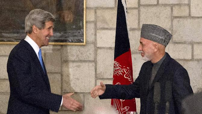 "Secretary of State John Kerry reaches to shakes hands with Afghan President Hamid Karzai at the end of their joint news conference at the Presidential Palace in Kabul, Monday, March 25, 2013. Kerry and Karzai made a show of unity Monday, shortly after the U.S. military ceded control of its last detention facility in Afghanistan, ending a longstanding irritant in relations between the two countries. Kerry, in Afghanistan for an unannounced visit, said he and Karzai were ""on the same page"" when it comes to peace talks with the Taliban. (AP Photo/Jason Reed, Pool)"