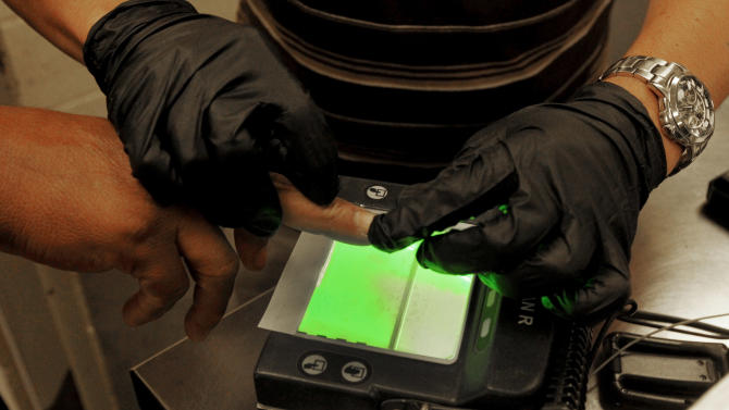 An illegal immigrant is fingerprinted as part of processing in order to create or update a file on that immigrant at Tucson Sector U.S. Border Patrol Headquarters Thursday, Aug. 9, 2012, in Tucson, Ariz.  The U.S. government has halted flights home for Mexicans caught entering the country illegally in the deadly summer heat of Arizona's deserts, a money-saving move that ends a seven-year experiment that cost taxpayers nearly $100 million.(AP Photo/Ross D. Franklin)
