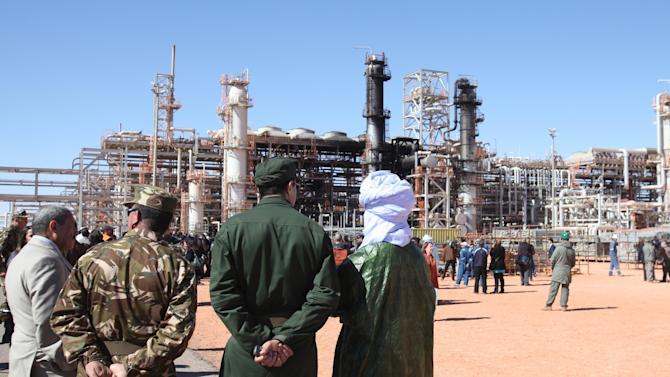 FILE - In this Jan 31, 2013 file photo, Algerian soldiers and officials stand in front of the gas plant in Ain Amenas, seen in background, during a visit organized by the Algerian authorities for news media. In an Oct. 3, 2012 internal al-Qaida letter found by the AP, international terrorist Moktar Belmoktar is excoriated for his unwillingness to follow orders and critiqued for his failure to carry out any large attack. His ego bruised, he quit and formed his own group to compete directly with his former employer. Within months, he claimed responsibility for two attacks, in Algeria and Niger, so large that they rivaled the biggest operations undertaken by al-Qaida's wing on the continent. In January, his cell penetrated a BP-operated gas plant in Algeria, kidnapping over 600 people, the largest hostage-crisis in recent memory. (AP Photo, File)