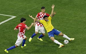 Brazil's Fred, right, falls after making contact…