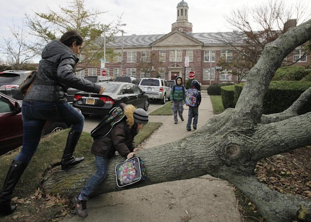 A woman and her son scramble over a tree toppled by Superstorm Sandy as she accompanies him to Public School 195, background, in the Manhattan Beach neighborhood of the Brooklyn borough, Monday, Nov.