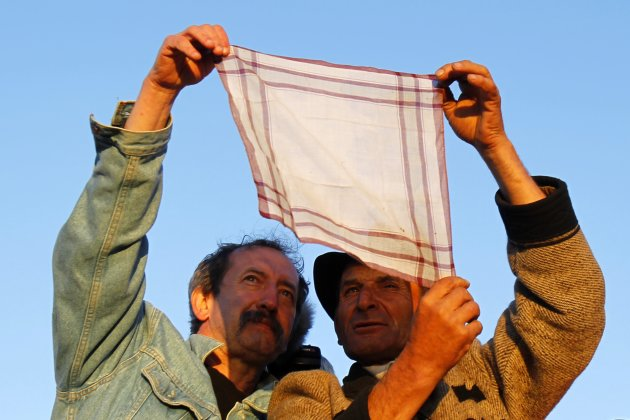 Ethnic Hungarians look at sunrise through a handkerchief during annual Roman Catholic Pentecostal pilgrimage gathering in Sumuleu Ciuc