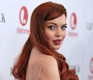 "FILE - In this Nov. 20, 2012 photo, actress Lindsay Lohan attends a dinner celebrating the premiere of ""Liz &amp; Dick"" at the Beverly Hills Hotel in Beverly Hills, Calif. Lohan is under arrest and charged with third-degree assault Thursday, Nov. 29, 2012 after police say she hit a woman during an argument at a New York City nightclub. (Photo by John Shearer/Invision/AP, File)"