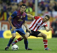 Barcelona's midfielder Sergio Busquets (L) fights for the ball with Athletic Bilbao's forward Oscar de Marcos during the Spanish King's Cup final football match at the Vicente Calderon stadium, in Madrid. Barcelona won 3-0