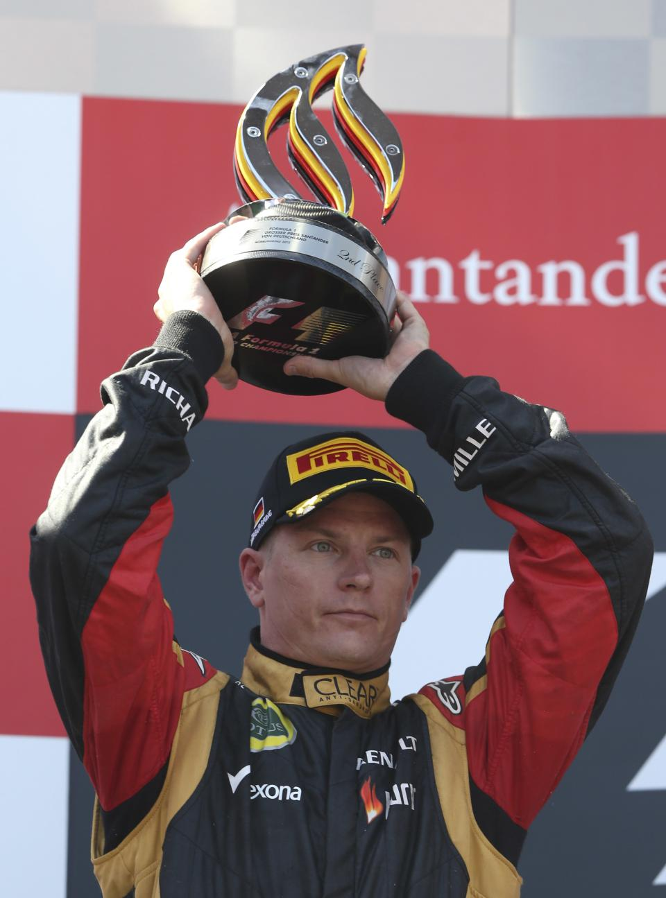 Second place Lotus driver Kimi Raikkonen of Finland holds the trophy on the podium after the German Formula One Grand Prix at the Nuerburgring racetrack, in Nuerburg, Germany, Sunday, July 7, 2013.(AP Photo/Luca Bruno)