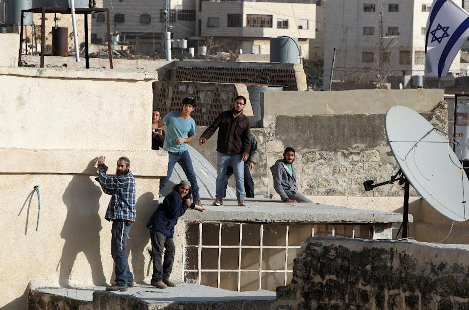 Israeli settlers stand on the roof of a building after dozens of Israeli Jews entered two homes in a building in the centre of the Palestinian city of Hebron, sparking violent clashes amid a disputed claim of ownership on January 21, 2016 (AFP Photo/Hazem Bader)