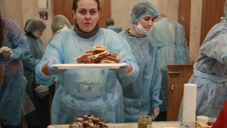 Volunteers prepare sandwiches for protesters inside City Hall in Kiev