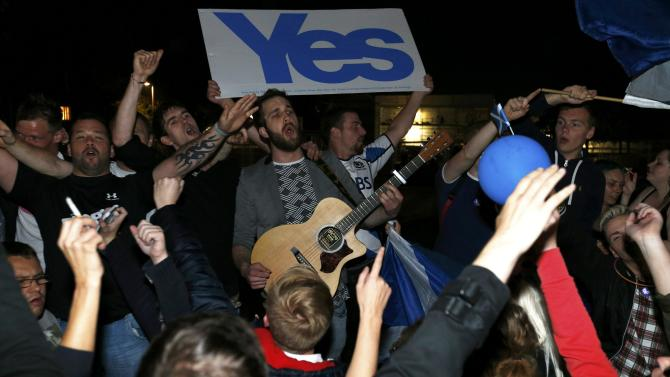 """Supporters from the """"Yes"""" Campaign sing outside the Scottish Parliament in Edinburgh, Scotland"""