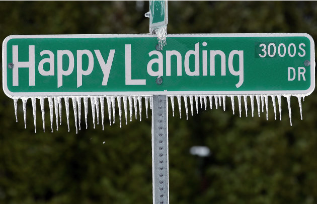 Icicles hang from a street sign after a fast moving snow storm blanketed central Illinois, Friday, Feb. 22, 2013, in Springfield, Ill. Powerful wind gusts created large snow drifts on many roadways, m