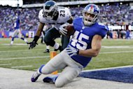 El fullback de los Giants de Nueva York Henry Hynoski (45) atrapa un pase para touchdown ante la defensa del cornerback de los Eagles de Filadelfia Dominique Rodgers-Cromartie (23) en la segunda mitad de un partido dede la NFL el domingo, 30 de diciembre del 2012. (Foto AP/Kathy Willens)