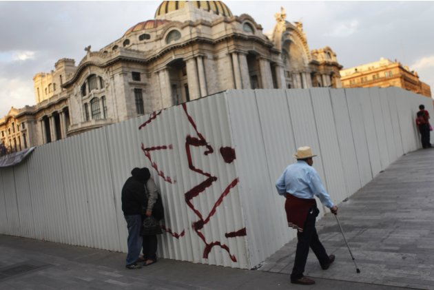A couple kiss as a man passes outside Bellas Artes palace in Mexico City