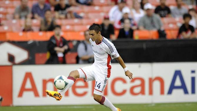 New England Revolution forward Diego Fagundez (14) kicks the ball against the D.C. United during the first half of an MLS soccer game, Saturday, July 27, 2013, in Washington