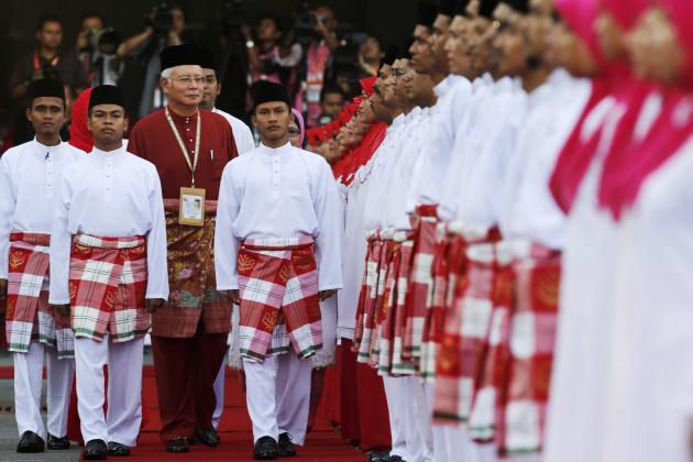 Malaysia's Prime Minister Najib Razak inspects the honour guard during the United Malays National Organisation party annual assembly at Putra World Trade Centre in Kuala Lumpur