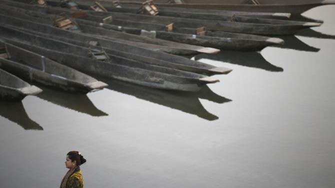 Boats are lined up as a woman stands on the bank of Rapti River at Sauraha in Chitwan