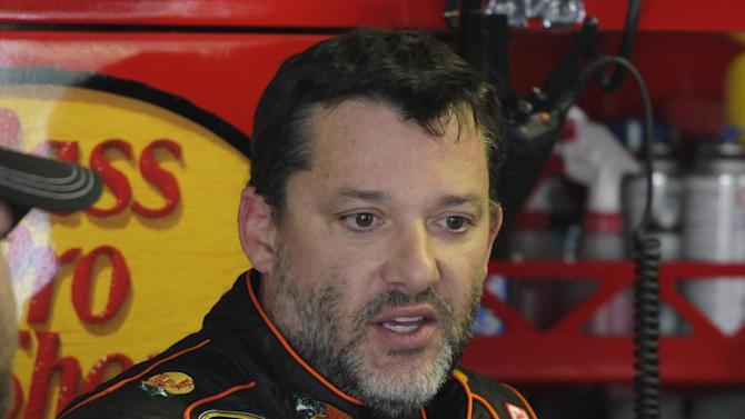 In this April 11, 2014, photo, Tony Stewart stands in the garage during practice for a NASCAR Sprint Cup series auto race at Darlington Speedway in Darlington, S.C. Authorities are investigating a serious crash that injured one person Saturday, Aug. 9, 2014, at a New York dirt track where Stewart was racing on the eve of a NASCAR race. (AP Photo/Mike McCarn)