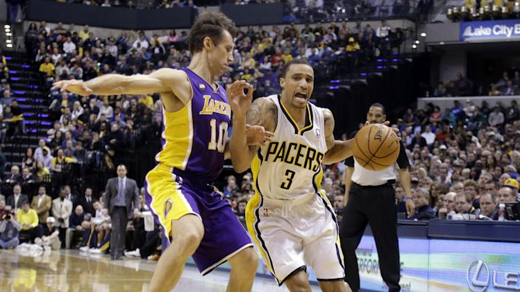 Indiana Pacers guard George Hill, is stopped on his drive to the basket by Los Angeles Lakers guard Steve Nash during the second half of an NBA basketball game in Indianapolis, Friday, March 15, 2013. The Lakers defeated the Pacers 99-93.  (AP Photo/Michael Conroy)