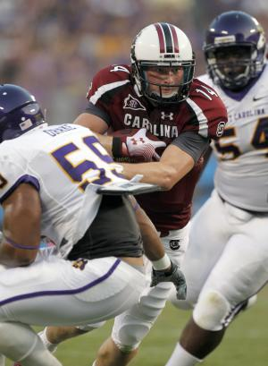 South Carolina quarterback Connor Shaw (14) fumbles the ball when he gets popped in between East Carolina's Daniel Drake (59) and Terry Williams (54) during the first half of an NCAA college football game in Charlotte, N.C., Saturday, Sept. 3, 2011. (AP Photo/Bob Leverone)