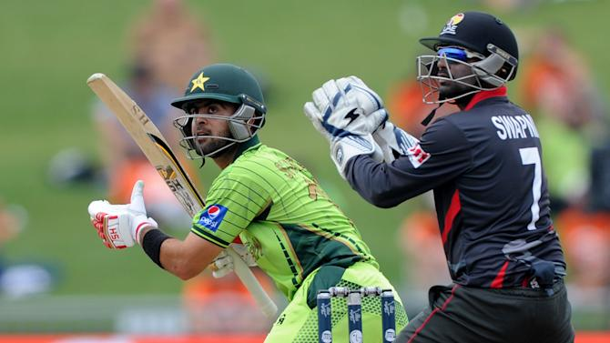 Pakistan batsman Ahmad Shahzad, left, plays a shot as United Arab Emirates wicketkeeper Swapnil Patil watches during their Cricket World Cup Pool B match in Napier, New Zealand, Wednesday, March 4, 2015. (AP Photo Ross Setford)