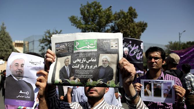 """A supporter of Iranian President Hassan Rouhani, holds a local newspaper with a headline that reads, """"historic call from a return flight,"""" upon his arrival from the U.S. near the Mehrabad airport in Tehran, Iran, Saturday, Sept. 28, 2013. Iranians from across the political spectrum hailed Saturday the historic phone conversation between President Barack Obama and Rouhani, reflecting wide support for an initiative that has the backing of both reformists and the country's conservative clerical leadership. (AP Photo/Ebrahim Noroozi)"""
