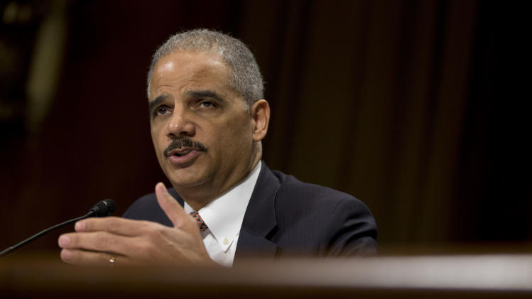 FILE – In this March 6, 2013, file photo  U.S.Attorney General Eric Holder testifies on Capitol Hill in Washington. Congress passed a spending bill to keep the government open through the end of September 2013, which Holder says provides no relief from the $1.6 billion in budget reductions that became effective March 1. In a memo to Justice Department employees he says he dealt with the problem by transferring $150 million in existing Justice Department funds to the Bureau of Prisons account, thus averting daily furloughs of 3,570 federal prison staffers around the country, and staving off what would have been a serious threat to the lives and safety of staff, inmates and the public.  (AP Photo/Evan Vucci, File)