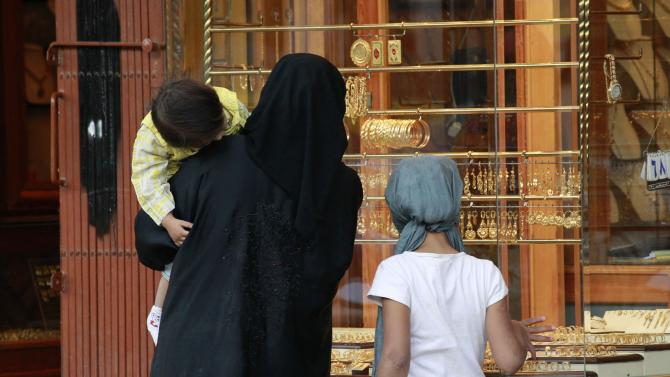Residents look at gold jewellery displayed at a shop window in Raqqa