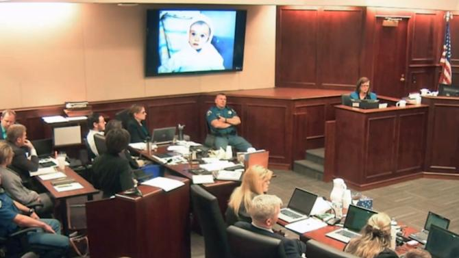 In this image made from Colorado Judicial Department video, Arlene Holmes, top right, the mother of James Holmes, fourth from left, in white shirt, gives testimony during the sentencing phase of the Colorado theater shooting trial in Centennial, Colo., on Wednesday, July 29, 2015. On the screen above is projected one of several family photos shown during her testimony, this one showing James Holmes when he was a toddler. (Colorado Judicial Department via AP, Pool)